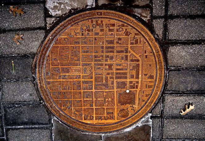 Oklahoma manhole covers have city maps on with a white dot showing where you are in the city